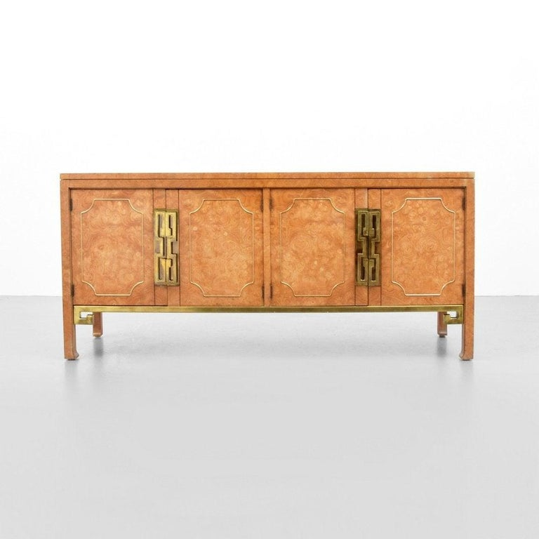 Iconic Mastercraft credenza in burl wood professionally refinished. This piece exudes midcentury at it's finest. The massive Greek Key pulls and stretcher details are incredible. And offers plenty of storage with two interior wide drawers and