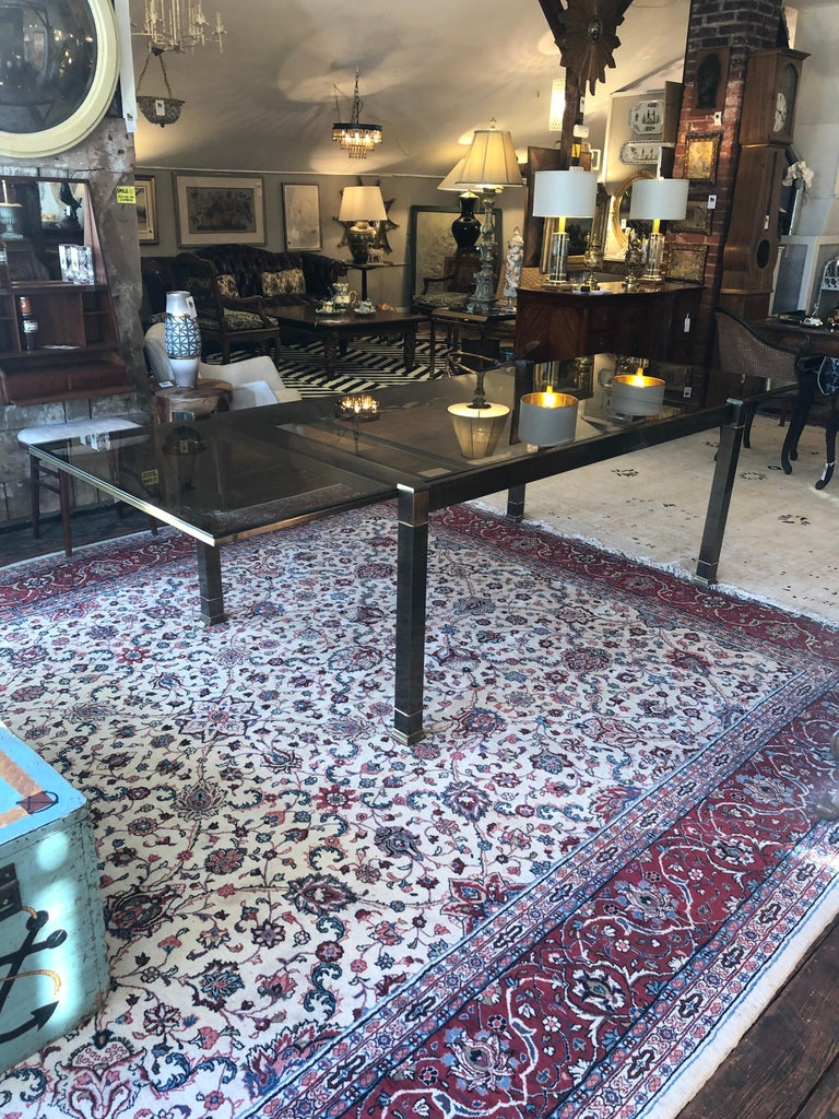 Ingeniously engineered Mid-Century Modern brass and warmly tinted glass expandable dining table with sleek design attributed to Mastercraft. Each end easily pulls out to open the central space where a central leaf raises up easily via an internal