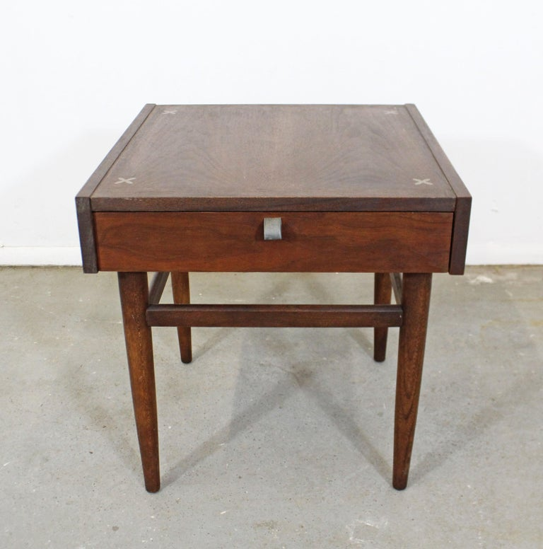 Offered is a vintage Mid-Century Modern walnut end table designed by Merton L. Gershun for American of Martinsville. Includes one drawer with a metal pull and features X-shaped brushed aluminium inlaid detailing in the tabletop. It is in good