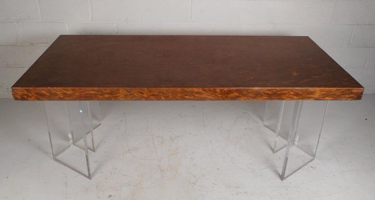 This gorgeous vintage modern dining table features a brushed metal top and a Lucite base. This one of a kind piece has two separate Lucite pieces supporting the table top. A sleek design with a brass and copper colored finish on the top. This table