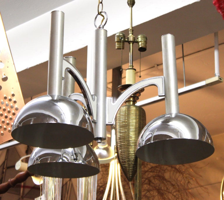 Mid-Century Modern ceiling pendant light made of metal with three shades around a center metal shaft. The piece has elements reminiscent of some machine age designs and was made in the mid-20th century. In great vintage condition with some