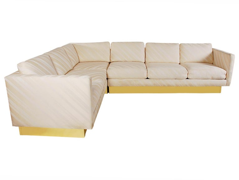 A lovely and chic looking sectional sofa attributed to Milo Baughman for Thayer Coggin. This L shaped sofa features it's original cream colored upholstery and brass-clad base.