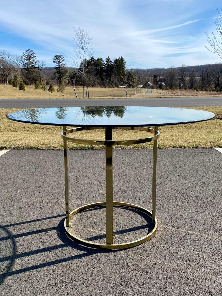 Mid-Century Modern brass and glass round dining or center hall table. Sleek style of Milo Baughman circa 1970s-1980s. This sculptural table features a shiny brass gold tone metal base with thick 1/2 inch round beveled glass
