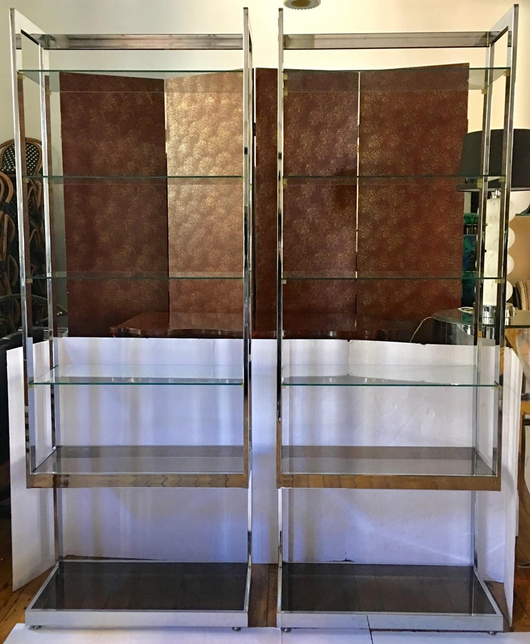 Mid-Century Modern Milo Baughman style flat bar polished chrome etageres. These 1970s Hollywood Regency style display shelving bookcase units feature two removable smoked glass bottom shelves and four removable clear glass upper shelves. Each