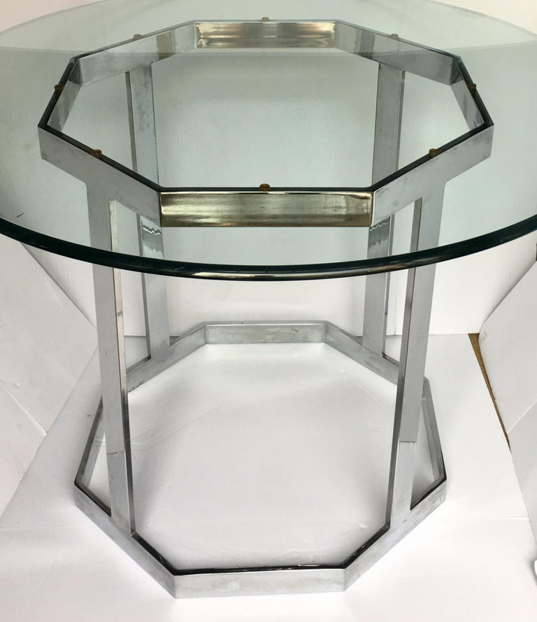1970s Mid-Century Modern chrome and glass dining or center table in the style of Milo Baughman. Sculptural polished chrome base features a flat bar octagon design. Existing round clear glass top is removable and can be replaced with a larger size