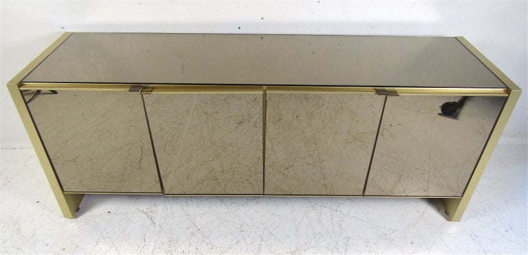 This stunning vintage modern credenza features ample room behind its four cabinet doors. A mirrored front and top makes this a unique addition to any home, business, or office. Please confirm item location (NY or NJ).