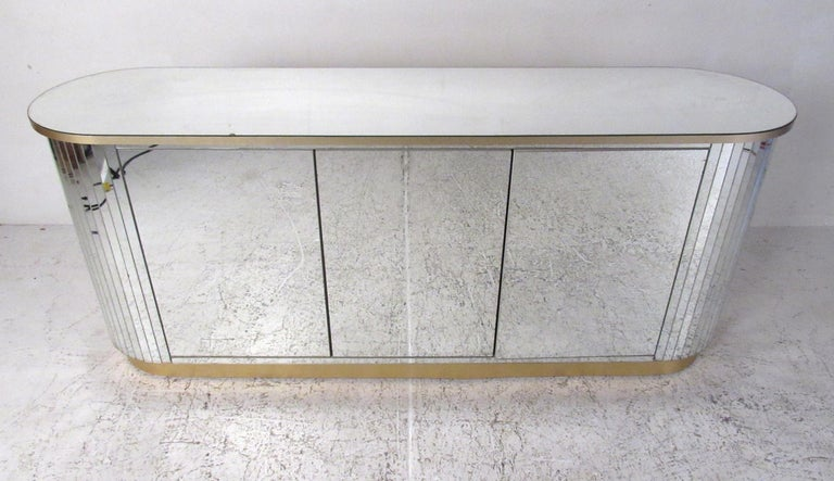 Mid-Century Modern mirrored three-door credenza with rounded sides and gold metal accent trim. The round sides are covered in mirrored strips creating a dramatic, faceted appearance. The white laminate interior features two adjustable shelves and