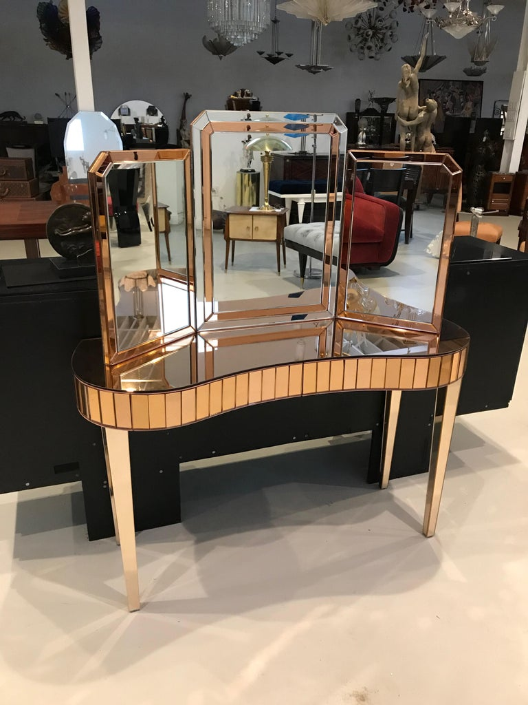 Mid-Century Modern mirrored vanity with matching mirror. The mirror can either be hung on the wall or can sit on the vanity. The vanity is all mirrored with an Art Deco motif. Having two draws for plenty of storage.