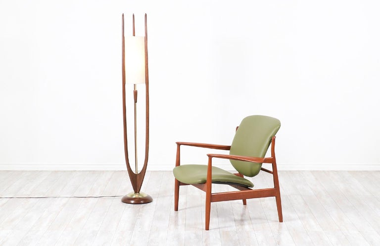 Dazzling floor lamp designed and manufactured by Modeline Lamp Co. in the United States circa 1960s. This sculptural lamp features a walnut wood frame accentuated with brass hardware and three tall prongs that support the new cylindrical linen