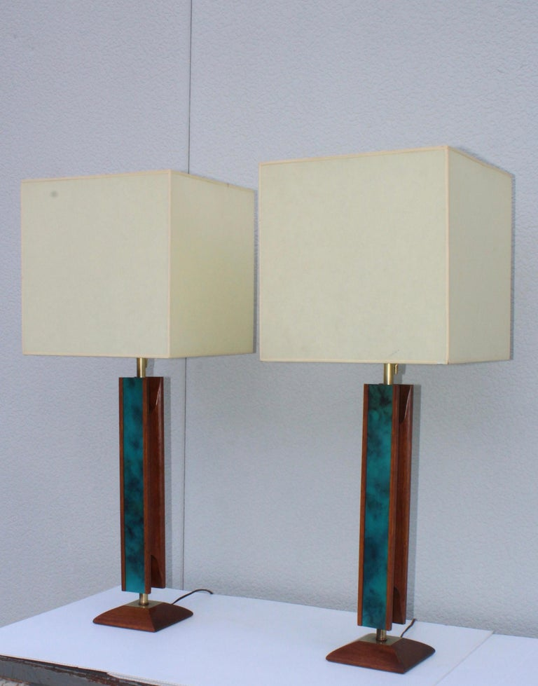 1960s Mid-Century Modern walnut and brass table lamps by Modeline. With enamel detail.  Measures: Height to light socket 27''.  Shades for photography only.
