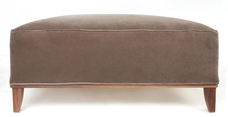Square midcentury mohair upholstered ottoman with wood base  Offered for sale is a Mid-Century Modern square ottoman that is upholstered in mohair velvet. The ottoman is supported by a wood frame with gracefully tapered legs.