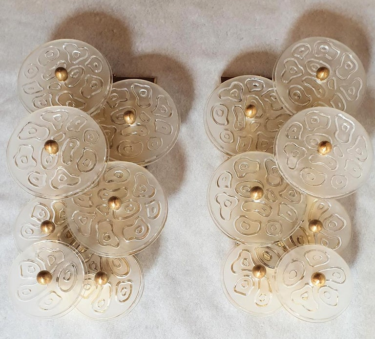 Mid-Century Modern clear Murano glass and brass sconces by Vistosi, Murano, Italy, 1960s, two pairs available. Sold and priced by pair. The vintage sconces have handmade thick, clear and frosted Murano glass discs, with a nice pattern in relief, and
