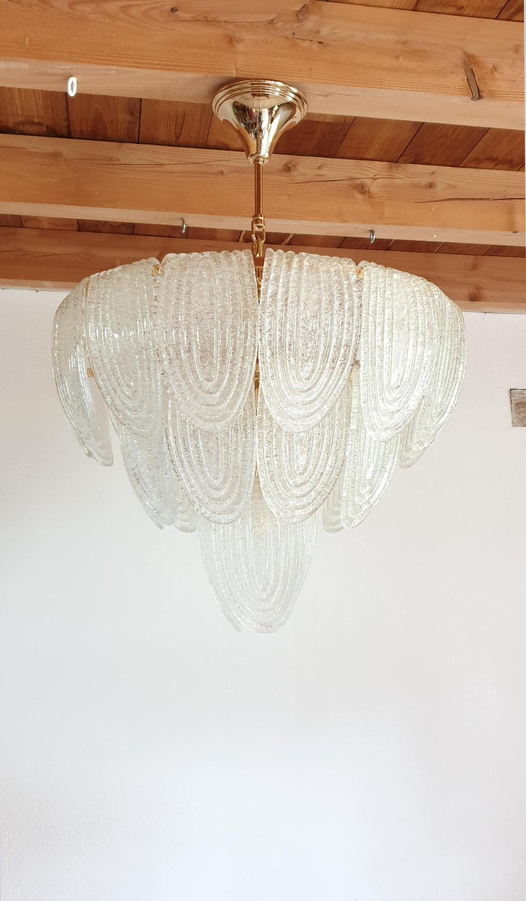 Mid-Century Modern translucent and textured Murano glass chandelier, with gold-plated frame. Two available; priced individually. Can be hanged as a flush mount fixture, or like a chandelier, with a gold-plated frame, chain and canopy: Total height