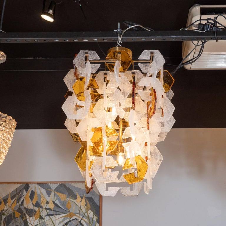 This stunning Mid-Century Modern chandelier was realized by the fabled Italian glass studio, Mazzega, in Murano, circa 1970. It features an abundance of interlocking three-sided geometric glass shades in translucent amber and semi opaque white glass