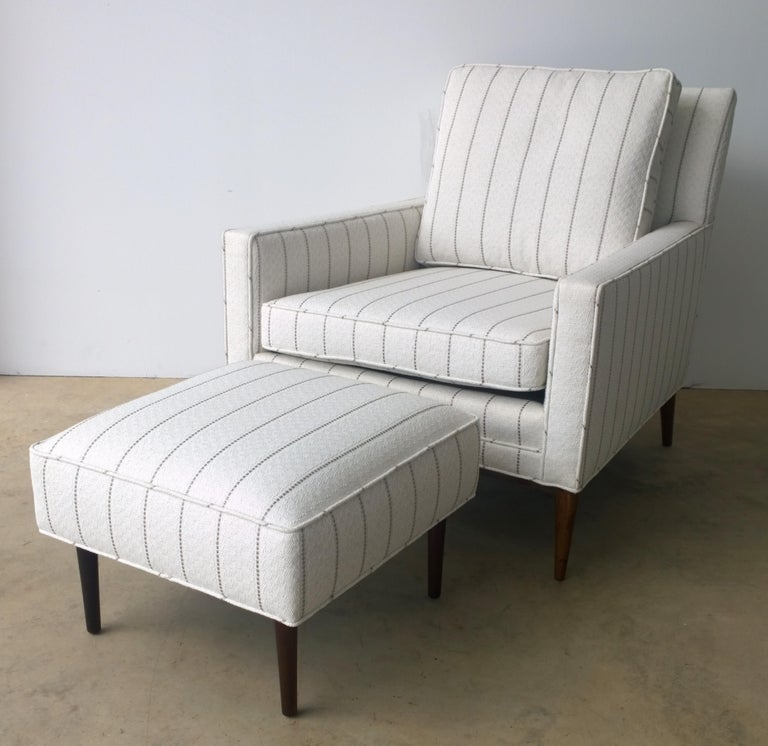 Offered is a Mid-Century Modern newly upholstered in white with a gray pin stripe Paul McCobb arm or lounge chair with Paul McCobb stool that was not originally sold with this chair. The chair is for sale and the stool is an extra newly upholstered