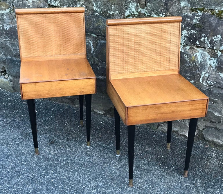 Rare pair of petite and refined nightstands designed by John Keal for Brown Saltman, circa 1950. Constructed of bleached mahogany with caned back panel and one drawer. The nightstands obtain their original black lacquer finish tapered legs and brass