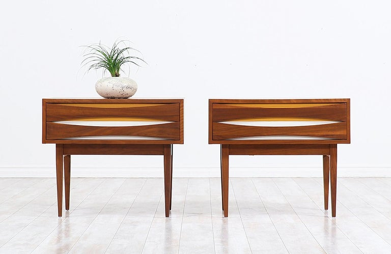 Elegant pair of modern nightstands designed and manufactured by West Michigan Furniture Co. in the United States circa 1950s. These lovely night stands feature a sturdy finished walnut wood standing on slim stiletto legs, adding a modern look to