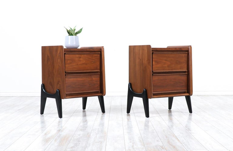Mid-Century Modern night stands with sculpted bases.