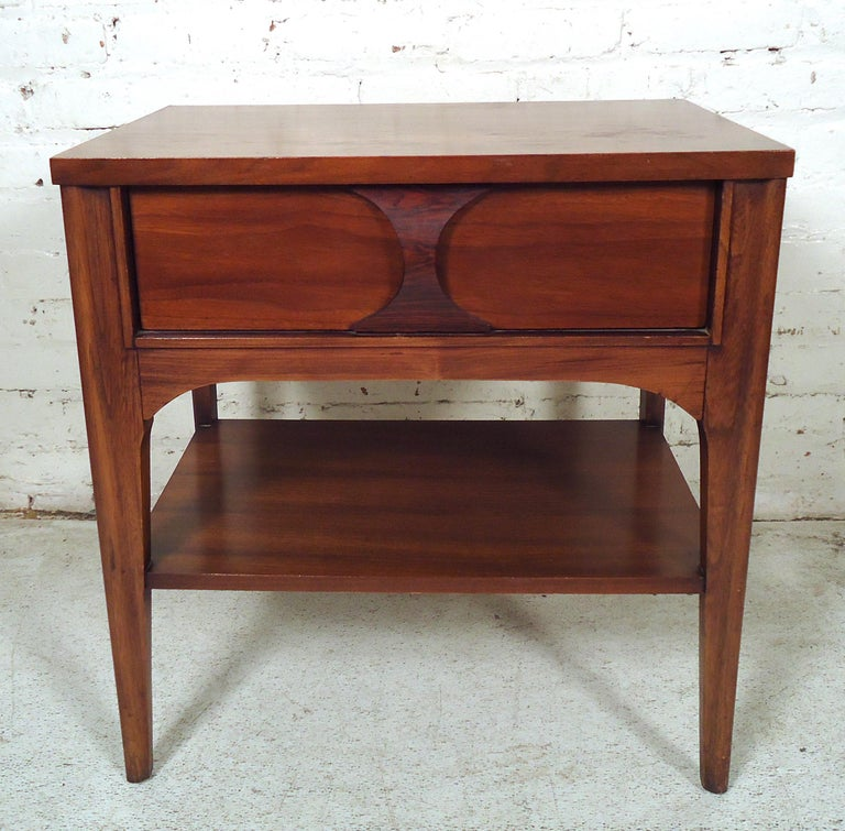 Unique single vintage modern nightstand featured in rich walnut grain and sculpted rosewood pull. This nightstand can be used in any bedroom or living room.