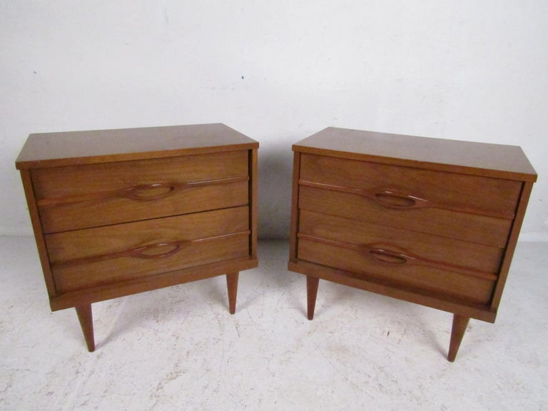 Stylish pair of Mid-Century Modern nightstands. Sturdily constructed frames with a nice walnut veneer exterior. Two drawers on each Stand with sculpted drawer pulls. This pair is sure to be a nice addition to any modern interior. Please confirm item