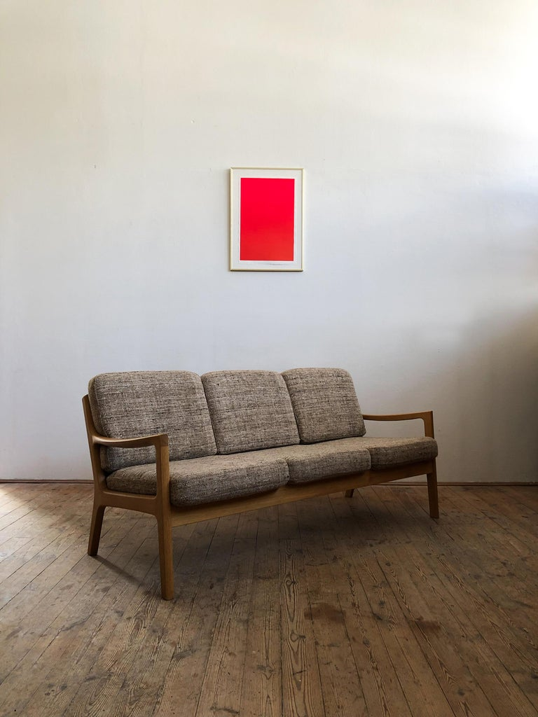 This shapely and comfortable sofa was designed by Ole Wanscher for Poul Jeppesens Møbelfabrik. This piece comes in a very rare version made of oakwood with foam cushions and woollen cover.