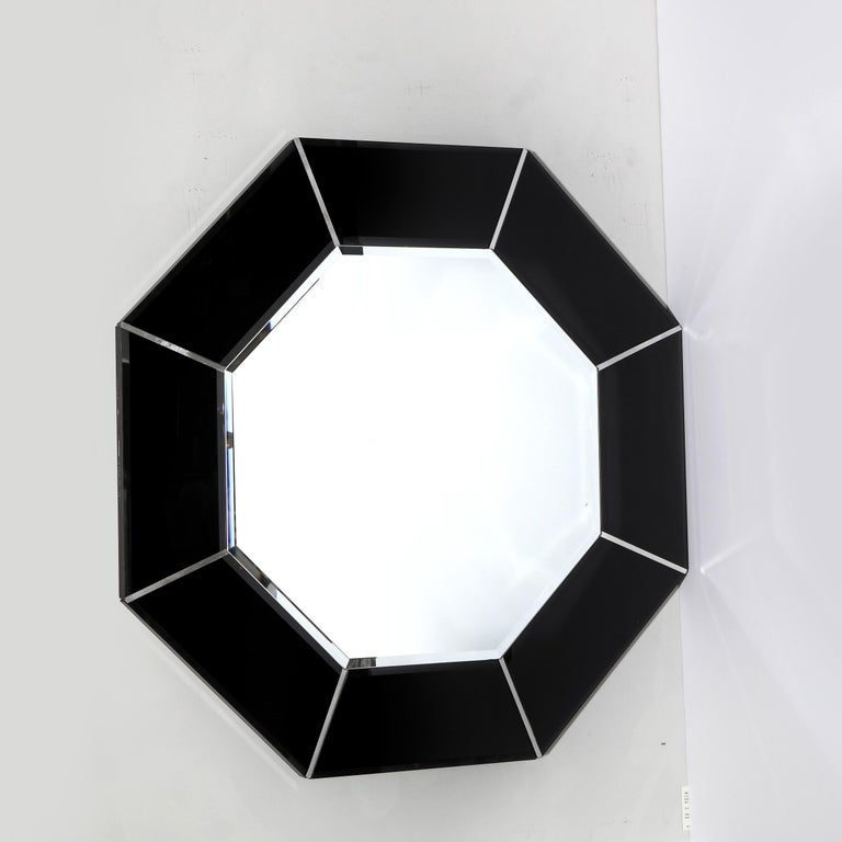 This graphic and refined Mid-Century Modern mirror was realized in the United States circa 1970. It feature an octagonal body with a smoked exterior composed of adjoining panels of graphite hued mirror separated by rectangular brushed aluminum