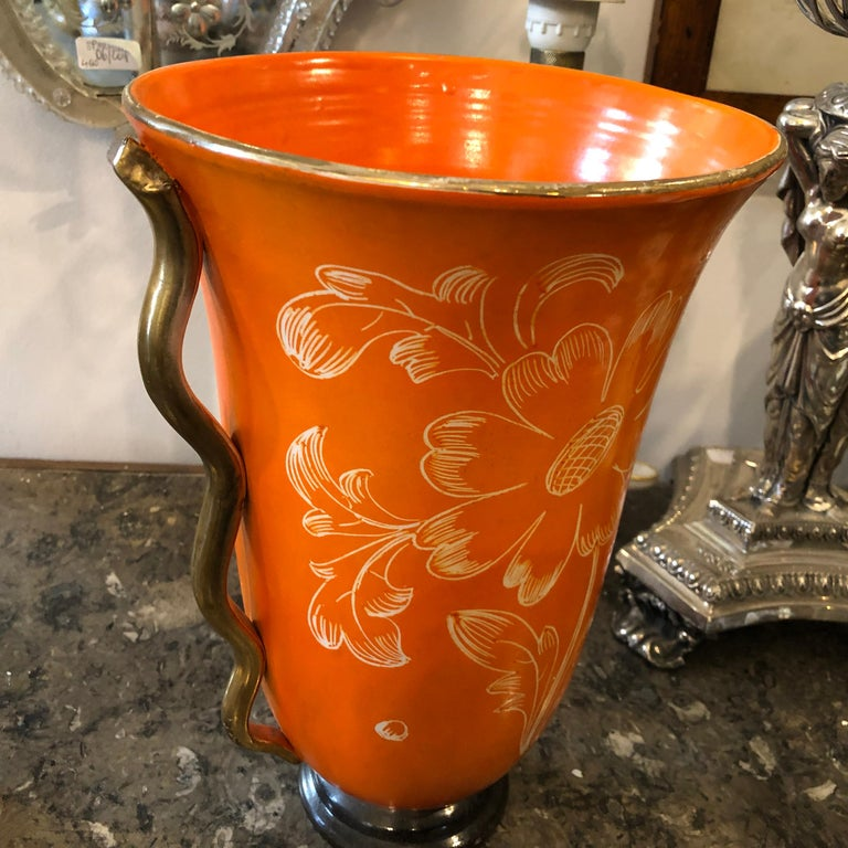 It's a rare vase made in Italy in the 1950s probably in Umbertide. Orange and gold ceramic, flowers decorated.