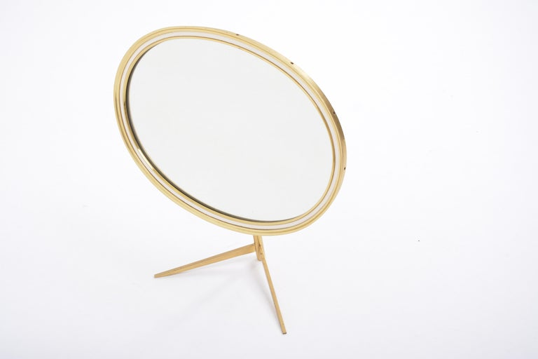Mid-Century Modern oval brass table mirror by Vereinigte Werkstätten This Mid-Century Modern table mirror features a solid brass stand and frame. The mirror can be adjusted to the desired angle. The backside of this table mirror is covered with