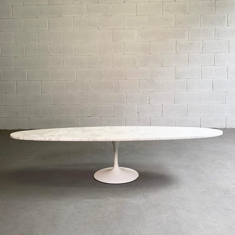 Mid-Century Modern, coffee table features an elongated oval marble top paired with a white tulip base.