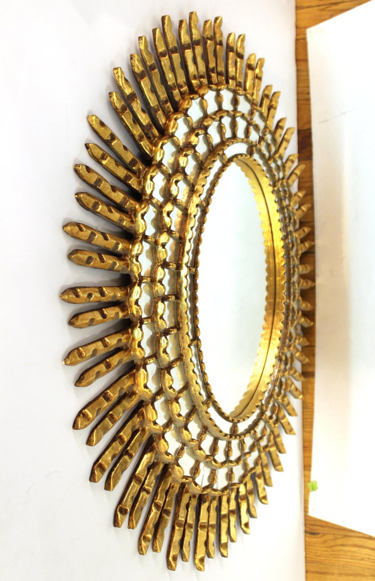 Mid-Century Modern oval shaped sunburst wall mirror. The piece is made of giltwood with inserted concentric circles of mirrored elements and wooden rays. In great vintage condition with age-appropriate wear and some minor cracks in the smaller