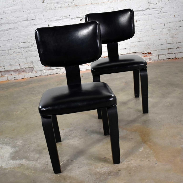 Handsome pair of Thonet bentwood Mid-Century Modern chairs in black with black vinyl upholstery. They are in good vintage condition. The vinyl does have a few cuts and nicks. The black painted wood shows age appropriate wear and patina. The