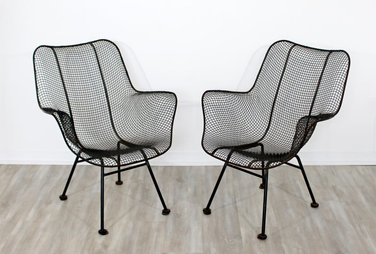 For your consideration is an original pair of black metal mesh patio armchairs, by Russell Woodard, circa the 1950s. In excellent condition. The dimensions are 27.5
