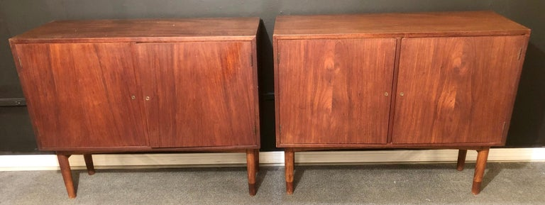 Mid-Century Modern pair of nightstands, cabinets or commodes by Gjovik Mobelfabriken. This fine sleek and stylish pair of Norwegian cabinets each bear a makers label on the back. The large impressive double doors open to show a finished shelved