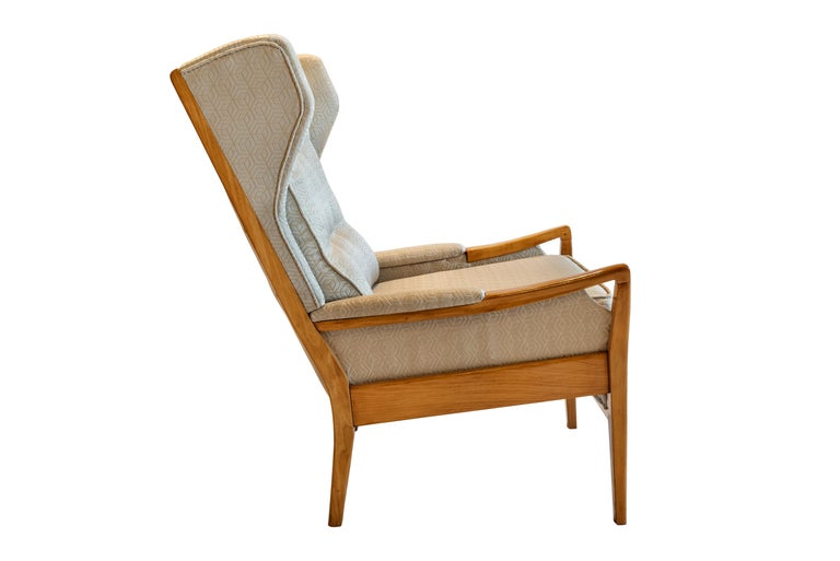 Mid-Century Modern pair of wingback teak chairs attributed to Arne Norell, circa 1958.  Super stylish and equally comfortable wingback, high back lounge chairs attributed to Swedish designer Arne Norell in the late 1950s. Raised on teak wood frames