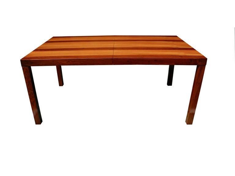 Newly refinished to bring out the natural woods, this parson table has an extra leaf 23.5 inches wide to extend the table. The leaf matches perfectly. Designed by Milo Baughman in rosewood, walnut and teak.