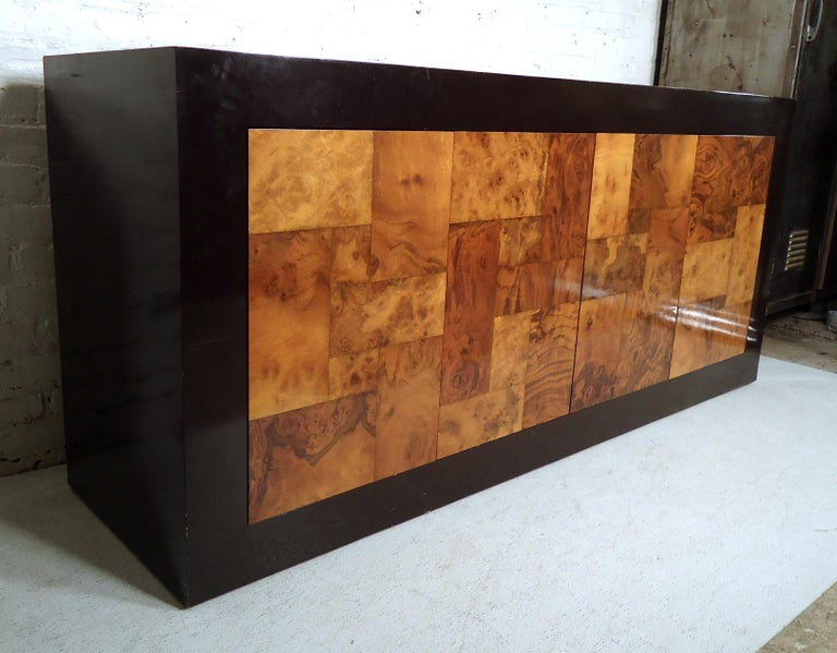 Sleek vintage modern credenza features spacious storage cabinets, small drawer, black lacquer body and burl wood doors. 