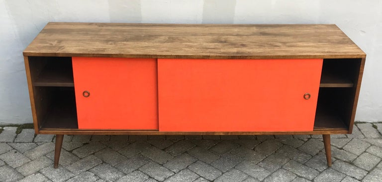 Very cool midcentury Paul McCobb credenza with vibrant orange grass cloth sliding doors, two adjustable shelves, plenty of storage and trademark tapered/angled legs, early 1950's. Original Paul McCobb Planner Group label on back. Professionally