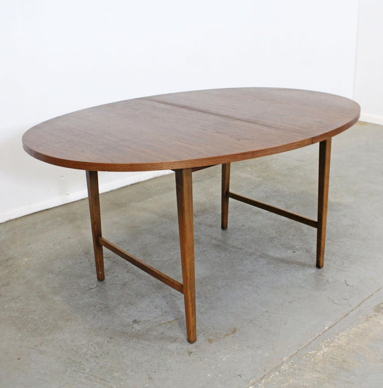 Offered is a round vintage Mid-Century Modern dining table attributed to Paul McCobb. This is a walnut dining table with a round top, includes one 12