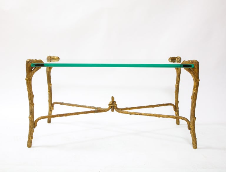A fabulous Mid-Century Modern P.E. GuerinFaux bois gilt bronze coffee table/center table with stretcher, signed. The top is a rectangular plate glass with gilt bronze stretcher base in the form of wood. The bottom is signed, E. Guerin, New
