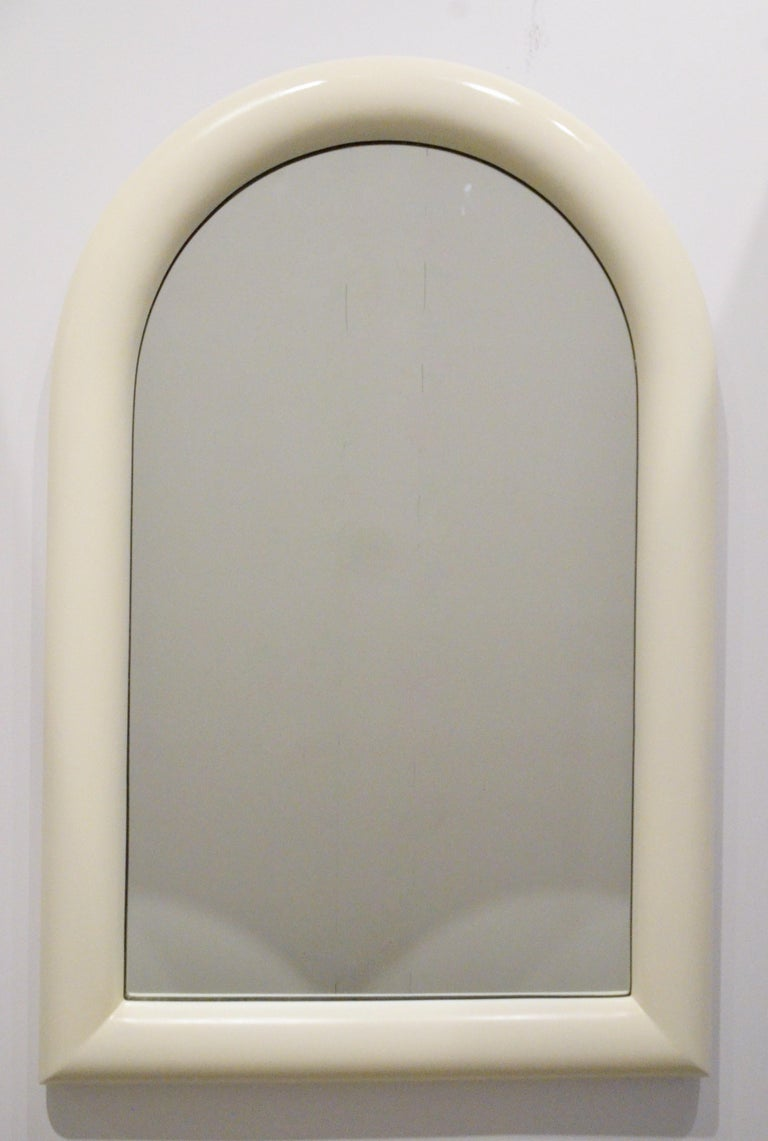 Offered is a Mid-Century Modern Pierre Cardin attributed arched topped wall mirror newly lacquered in a creamy white wood frame. Pierre Cardin's signature style of futuristic forms combined with traditional finishes are echoed in this piece. This