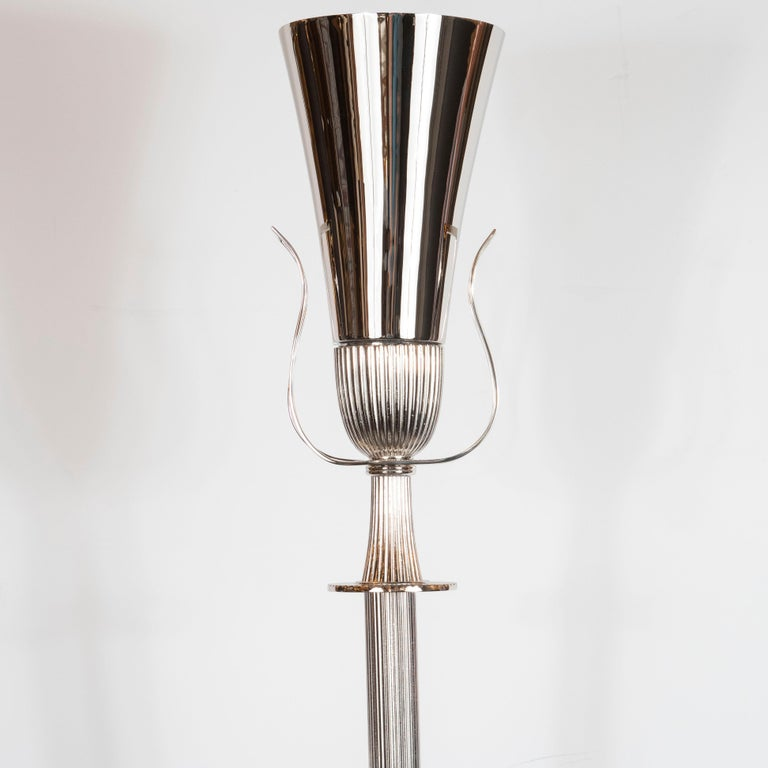 This elegant Mid-Century Modern torchère was realized by the fabled 20th century design luminary Tommi Parzinger in the United States, circa 1950. It features a reeded body that attaches to an hourglass form neck with undulating open form