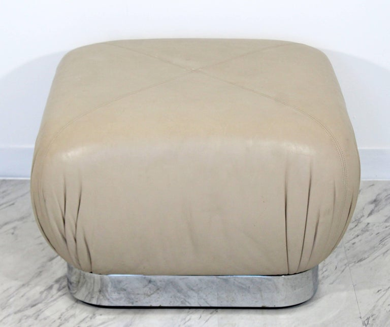 For your consideration is a gorgeous, beige leather and chrome ottoman, on wheels, by Preview Furniture, circa the 1970s, in the style of Karl Springer. In excellent condition. The dimensions are 24