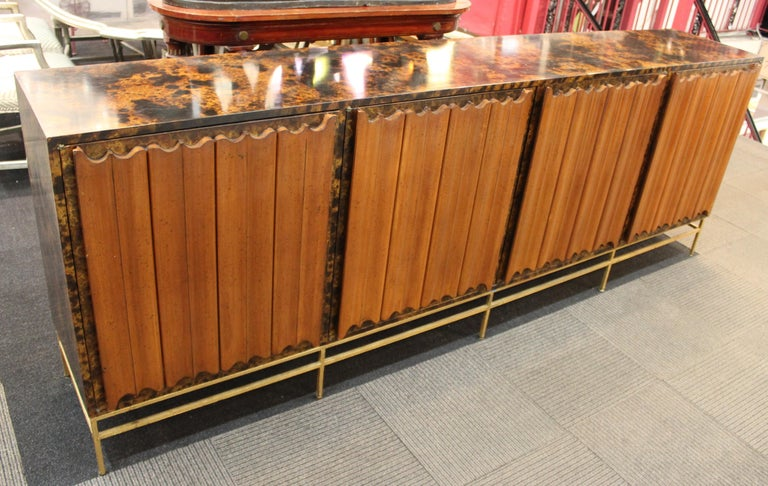 Monumental American Mid-Century Modern credenza or sideboard in the style of Harvey Probber, with tortoiseshell finish and four linen-fold style front panel doors atop a gilt metal frame. The piece dates from the mid-20th century and is in great