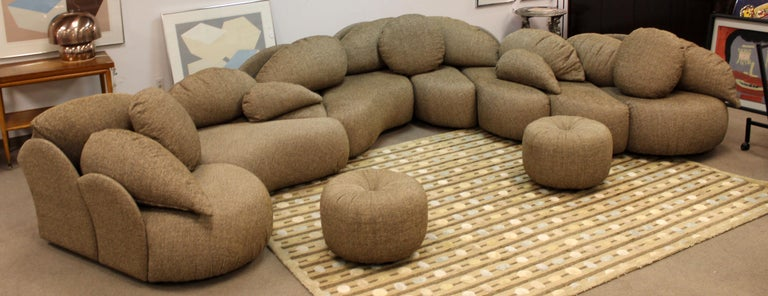 For your consideration is a wonderfully unique, large sectional sofa, with a sculptural design and two round ottomans, by Roche Bobois. Can be configured in any way to fit your needs. Extremely comfortable. Fabric and structure is in EXCELLENT