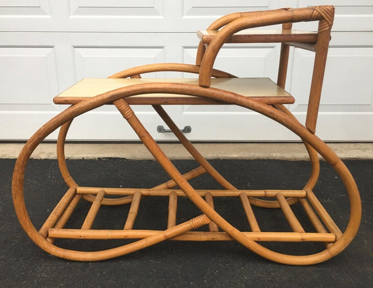 Three quarter pretzel rattan side table in original vintage condition. Features amazing organic and sculptural bentwood bamboo wood frame. Features three tiers, top two table tiers are hardwood tops covered in original blonde laminate. Bottom tier