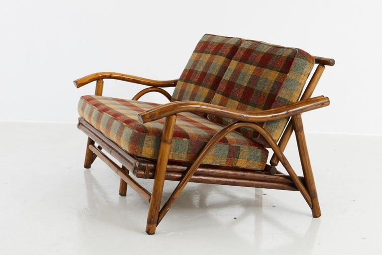 Vintage settee/loveseat with serpentine arms, in the style of John Wisner for Ficks Reed, 1950s. Very well executed rattan and hardwood construction, with spring support, beautiful textured and colored cushions in very good condition. The