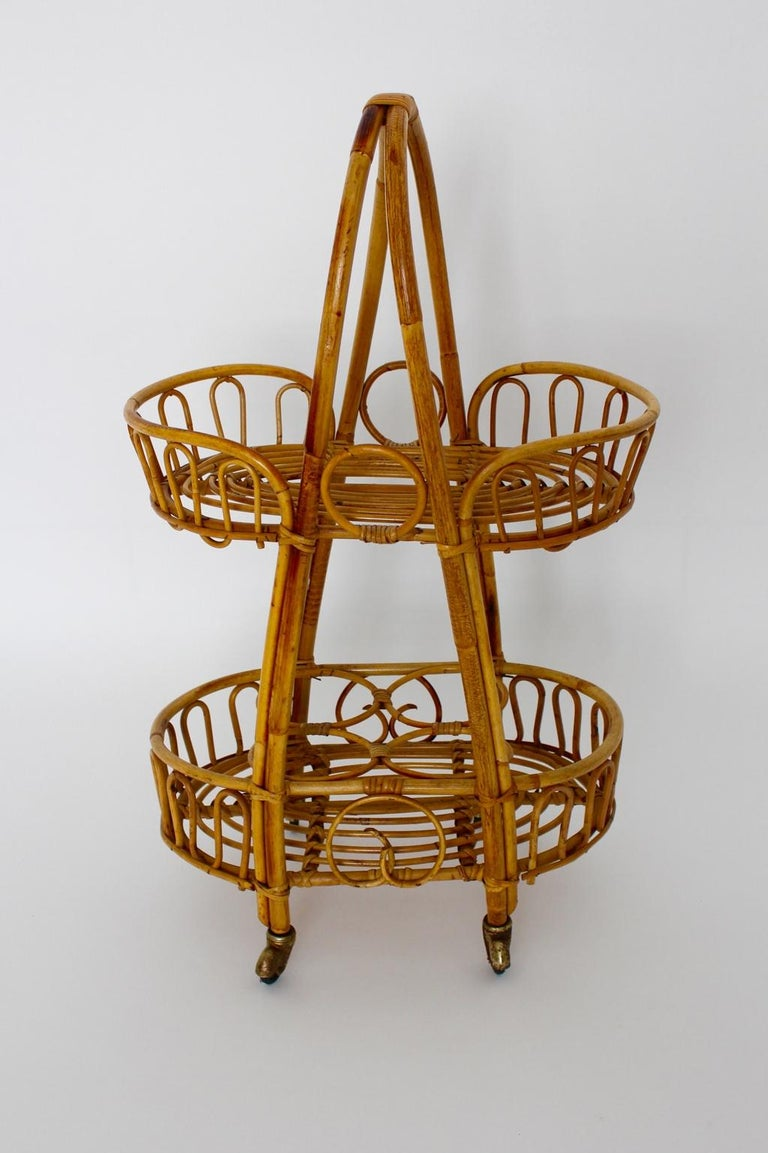 This presented cute rattan vintage bar cart from the 1950s was designed and made in Italy. Furthermore the bar cart is usable not only for bottles and beverages also to storage your beloved books or plants. Additionally the bar cart features 4 small