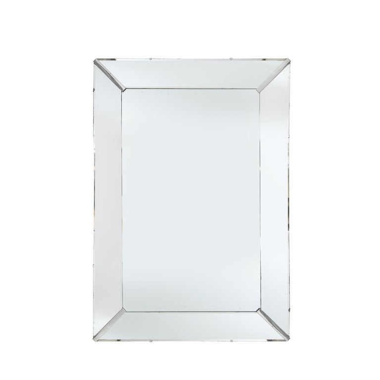 This stunning Mid-Century Modern mirror was realized in the United States, circa 1950. It features a shadowbox form in a rectangular silhouette with beveled plain mirror segments secured in the corner with chrome inserts. With its austere form and