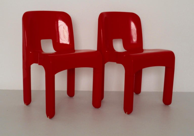 This set of 2 red plastic dining chairs Model No. 4860 Universale was designed by Joe Colombo 1965-1967. Also the dining chairs were produced by Kartell, Noviglio, Milano. You see the label underneath. The vintage condition is very good with