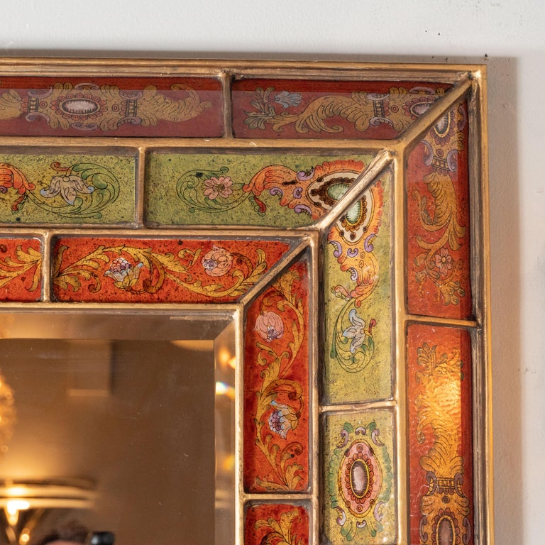This refined and sophisticated shadowbox mirror was realized in Venice, Italy, circa 1950. The piece offers a mosaic of hand-painted panels- with notched giltwood perimeters- in alternating tones of cinnabar red and olive. Each panel has been hand